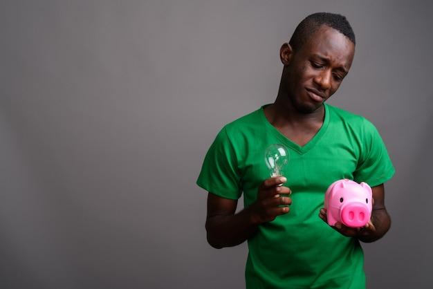 Jovem africano, vestindo camisa verde na parede cinza