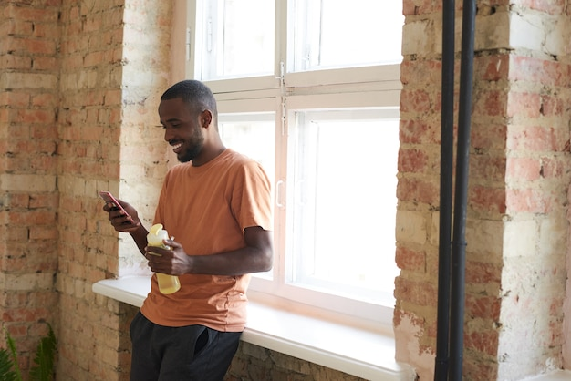 Jovem africano vestindo roupas esportivas, bebendo água e usando telefone celular após o treino na academia