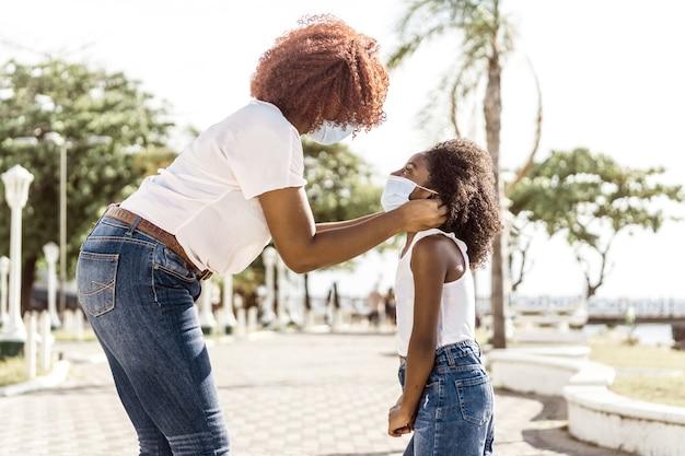 Jovem afro-americana ajudando a filha a colocar uma máscara facial ao ar livre
