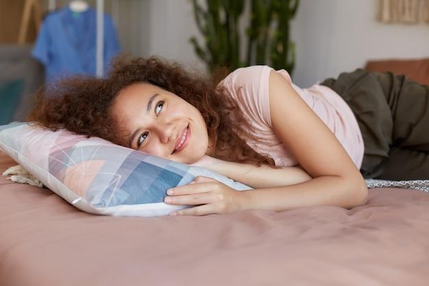 Jovem afro-americana alegre deitada na cama, aprecia a manhã ensolarada em casa, sorrindo amplamente e olhando para cima de maneira dramática.