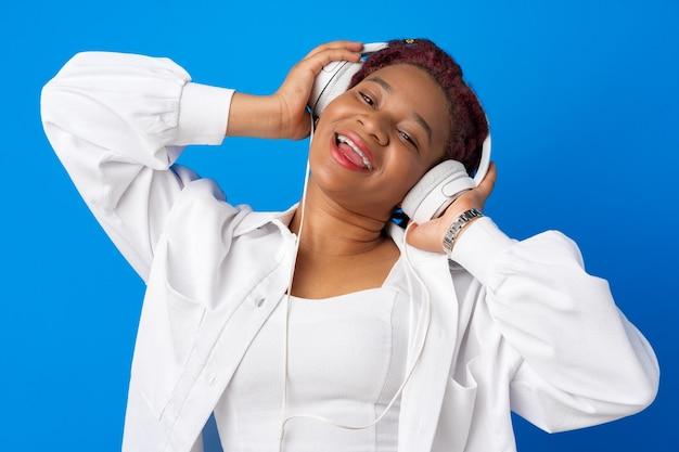 Jovem afro-americana alegre ouvindo música com fones de ouvido contra um fundo azul