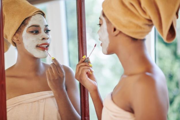Jovem afro-americana atraente com máscara de lama para limpar os poros no rosto, em frente ao espelho e aplicando brilho labial