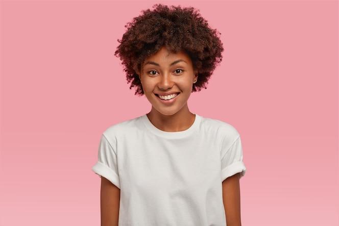 Jovem afro-americana atraente com sorriso carinhoso, mostra os dentes brancos, vestida com uma camiseta casual simulada