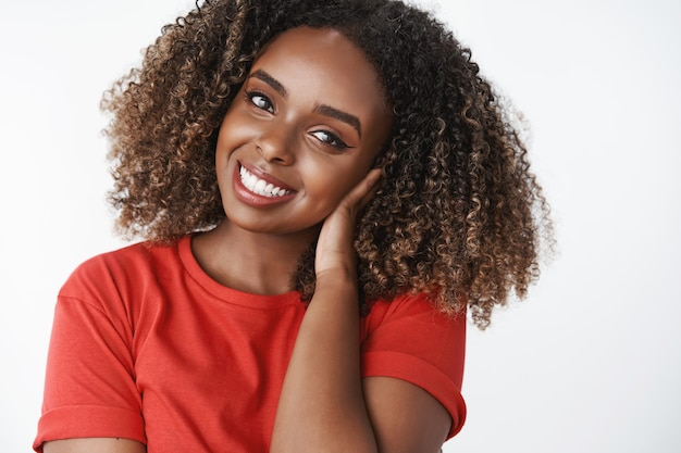Jovem afro-americana atraente e terna, de aparência amigável, com penteado afro encaracolado, penteando o cabelo com a mão suavemente, inclinando a cabeça e sorrindo adorável na frente com um olhar carinhoso e sedutor