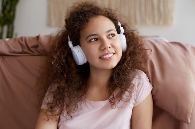 Jovem afro-americana cacheada, amplamente sorri e ouvindo música favorita em fones de ouvido, aproveitando o dia e olhando para longe.