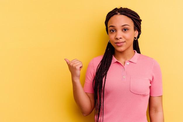 Jovem afro-americana chocada apontando com o dedo indicador