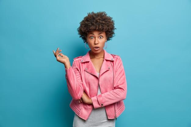Jovem afro-americana chocada preocupada tem expressão de vergonha surpresa, mantém os olhos bem abertos, estar bem vestida, preocupada com alguma coisa, expressa grande descrença, fica em pé