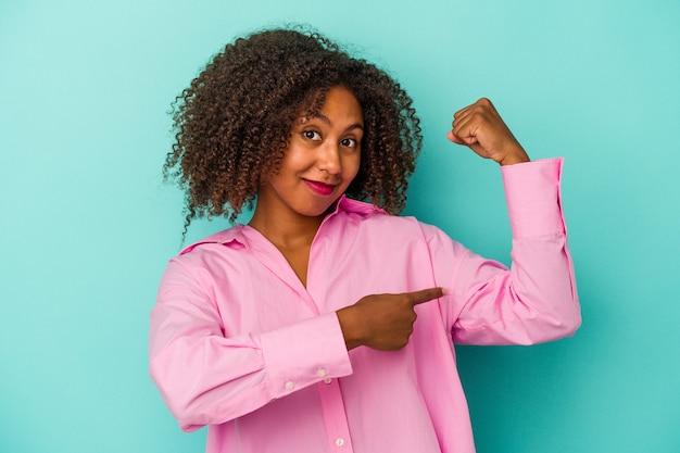 Jovem afro-americana com cabelo encaracolado isolado em um fundo azul, mostrando força gesto com os braços, símbolo do poder feminino.