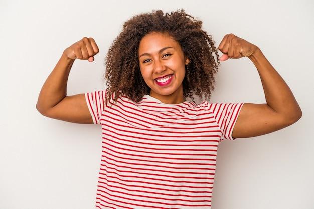 Jovem afro-americana com cabelos cacheados, isolado no fundo branco, mostrando força gesto com os braços, símbolo do poder feminino.