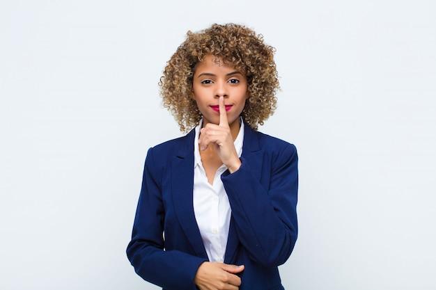 Jovem afro-americana com cara de sério e zangada com o dedo pressionado nos lábios, exigindo silêncio ou silêncio, mantendo um segredo na parede plana