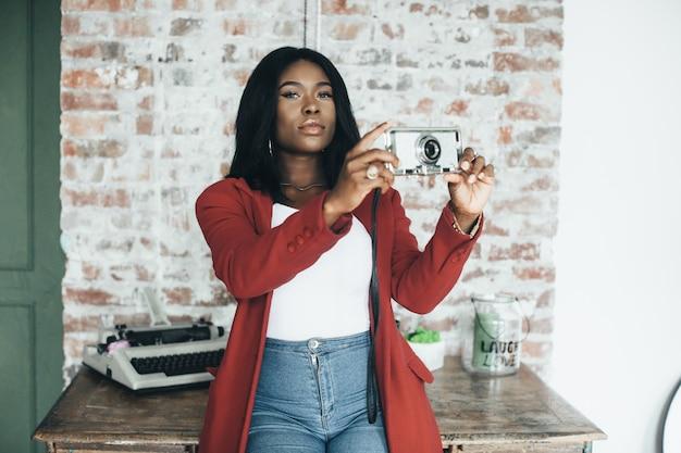 Jovem afro-americana com casaco vermelho em meio urbano segura o telefone em suas mãos e faz fotos