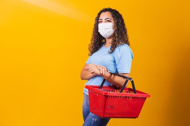 Jovem afro-americana com tranças, usando uma cesta de compras e uma máscara médica