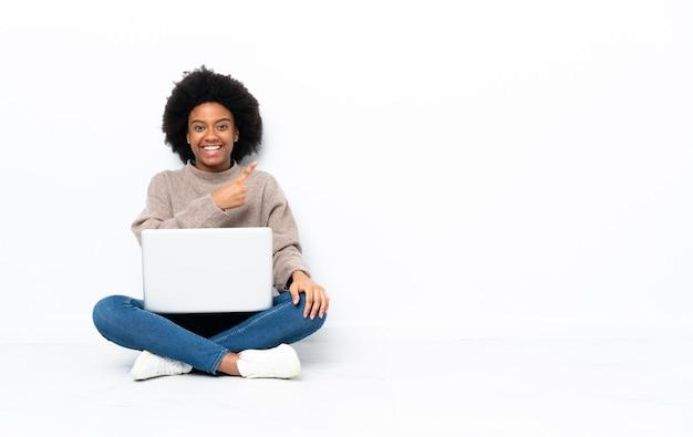 Jovem afro-americana com um laptop sentada no chão apontando para o lado para apresentar um produto