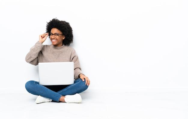 Jovem afro-americana com um laptop sentada no chão com óculos e feliz