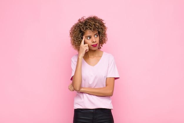 Jovem afro-americana com um olhar concentrado, imaginando com uma expressão duvidosa, olhando para cima e para o lado na parede rosa