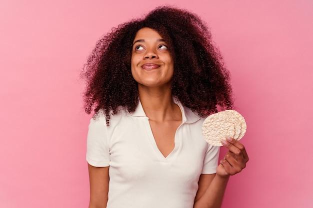 Jovem afro-americana comendo um bolo de arroz isolado na rosa, sonhando em alcançar objetivos e propósitos