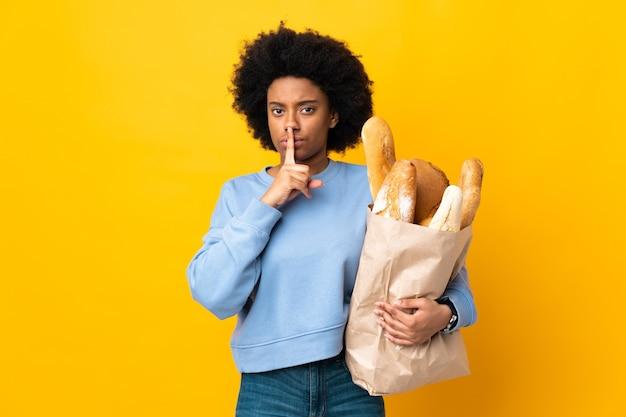 Jovem afro-americana comprando algo pão isolado em amarelo mostrando sinal de silêncio gesto colocando o dedo na boca
