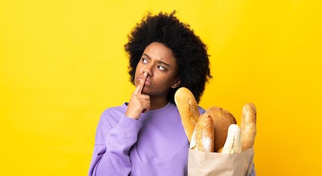Jovem afro-americana comprando pão isolado em amarelo tendo dúvidas enquanto olha para cima