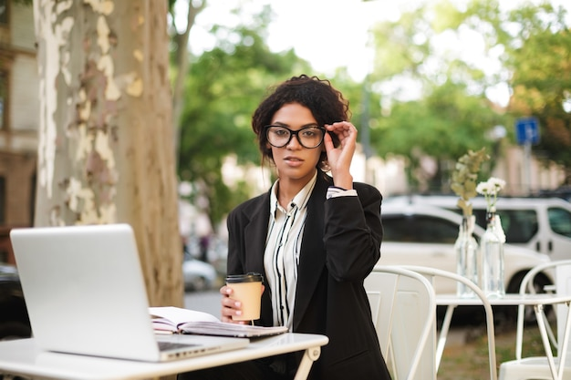 Jovem afro-americana de óculos, sentada à mesa do café com uma xícara de café na mão e o laptop na mesa