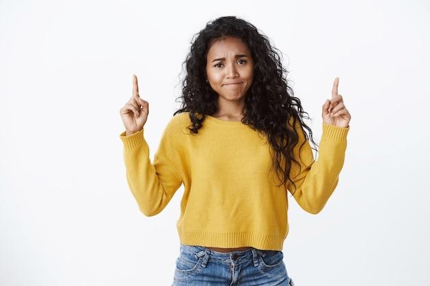 Jovem afro-americana decepcionada franzindo os lábios franzindo a testa e apontando para cima insatisfeita, dando feedback negativo, parecendo cética e impressionada, suéter branco de parede amarelo em pé