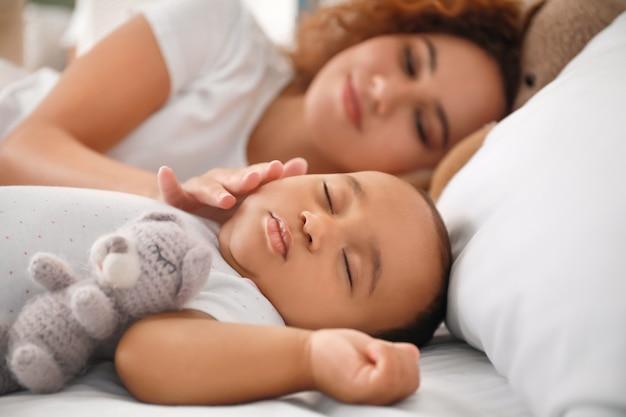 Jovem afro-americana e seu bebê dormindo na cama