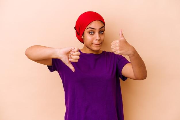 Jovem afro-americana em bege, mostrando os polegares para cima e para baixo, difícil escolher o conceito