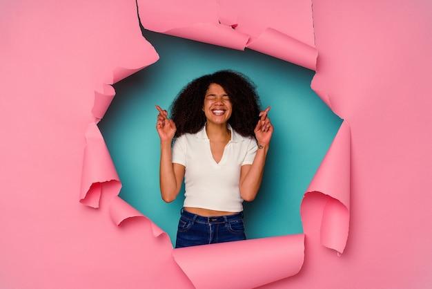 Jovem afro-americana em papel rasgado, isolado em um fundo azul, cruzando os dedos para ter sorte