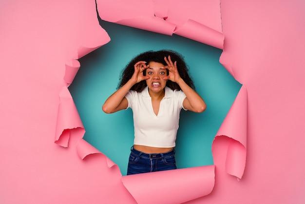 Jovem afro-americana em papel rasgado, isolado em um fundo azul, mantendo os olhos abertos para encontrar uma oportunidade de sucesso.