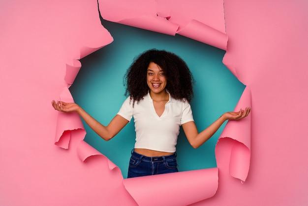 Jovem afro-americana em papel rasgado, isolado em um fundo azul, mostrando uma expressão de boas-vindas.