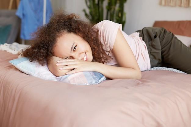 Jovem afro-americana encaracolada bonita na cama, parece feliz, aproveita o dia ensolarado em casa e amplamente sorri.