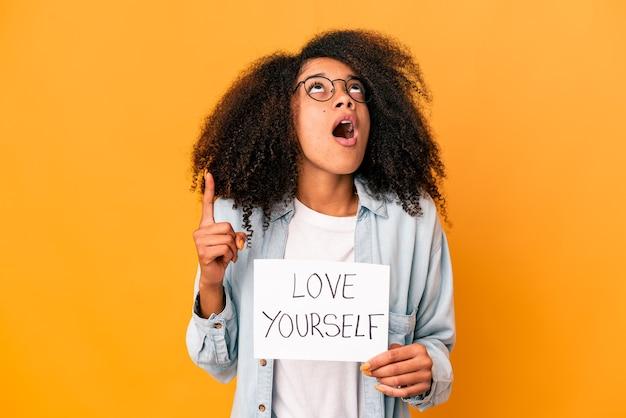 Jovem afro-americana encaracolada segurando um cartaz de amor a si mesmo apontando para cima com a boca aberta.