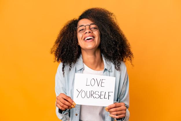 Jovem afro-americana encaracolada segurando um cartaz de amor a si mesmo