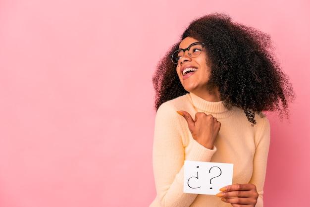 Jovem afro-americana encaracolada segurando um cartaz de dúvida