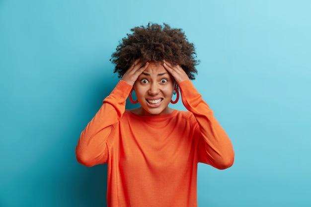 Jovem afro-americana estressada agarra a cabeça aperta os dentes tem problemas para estar em pânico não sabe o que fazer sofre uma dor de cabeça insuportável usa um macacão casual isolado sobre a parede azul.