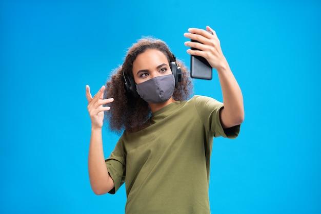 Jovem afro-americana falando em videochamada usando seu smartphone com fones de ouvido em uma camiseta verde-oliva, máscara facial reutilizável