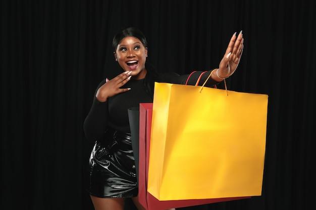 Jovem afro-americana fazendo compras com embalagens coloridas em preto