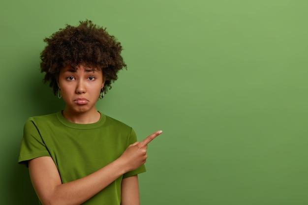 Jovem afro-americana insatisfeita e infeliz, triste por perder uma boa oportunidade, não tem dinheiro para comprar coisas caras, parece chateada e insatisfeita, franze a testa e fica de mau humor, usa uma camiseta verde casual.