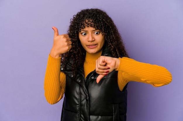 Jovem afro-americana isolada com os polegares para cima e os polegares para baixo, difícil escolher o conceito