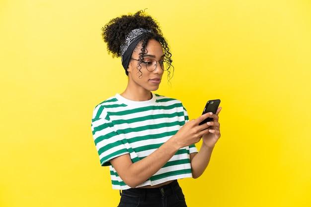 Jovem afro-americana isolada em fundo amarelo enviando uma mensagem ou e-mail com o celular
