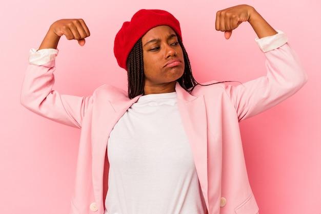 Jovem afro-americana isolada em fundo rosa mostrando força gesto com os braços, símbolo do poder feminino.