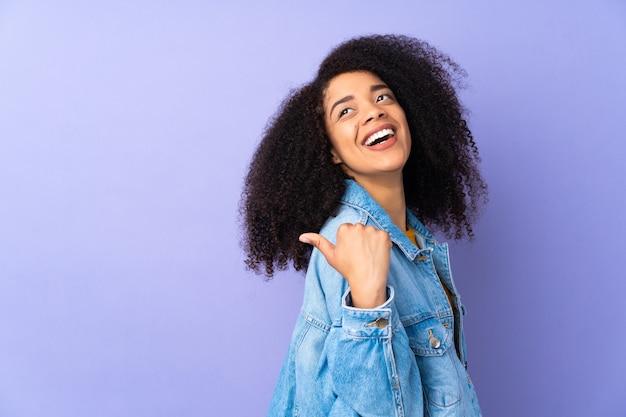 Jovem afro-americana isolada em roxo apontando para o lado para apresentar um produto