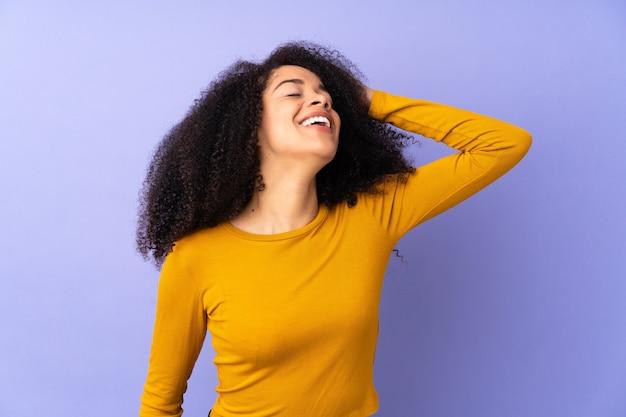 Jovem afro-americana isolada em roxo sorrindo muito