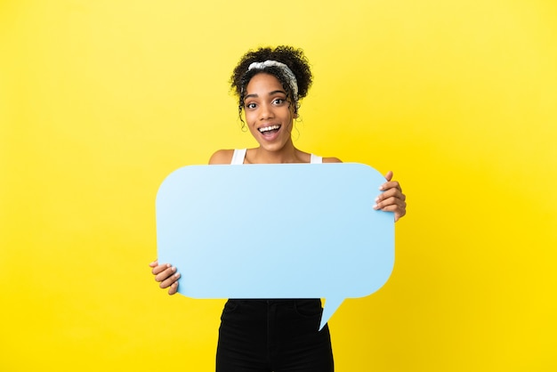 Jovem afro-americana isolada em um fundo amarelo segurando um balão de fala vazio com expressão de surpresa
