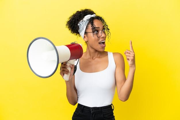 Jovem afro-americana isolada em um fundo amarelo segurando um megafone e pretendendo descobrir a solução