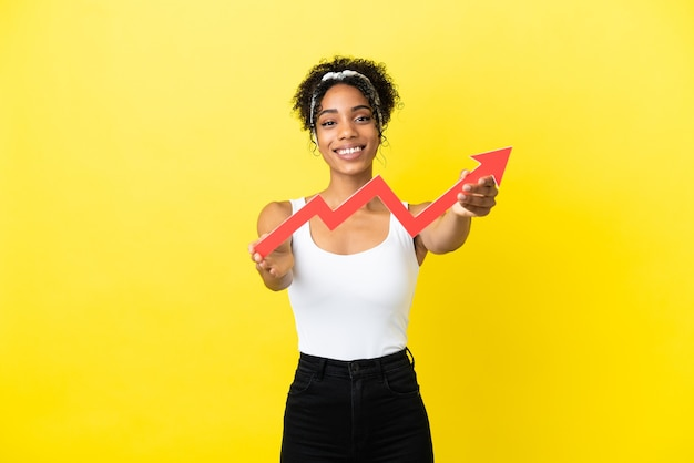 Jovem afro-americana isolada em um fundo amarelo segurando uma flecha ascendente com uma expressão feliz.