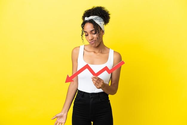 Jovem afro-americana isolada em um fundo amarelo segurando uma seta para baixo e com uma expressão triste