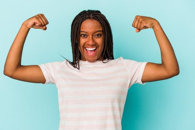 Jovem afro-americana isolada em um fundo azul, mostrando um gesto de força com os braços, símbolo do poder feminino.
