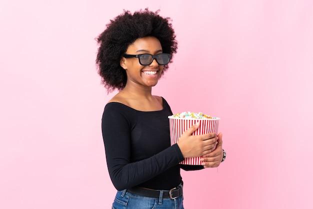 Jovem afro-americana isolada em um fundo rosa com óculos 3d e segurando um grande balde de pipocas