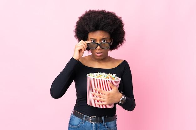 Jovem afro-americana isolada em um fundo rosa surpresa com óculos 3d e segurando um grande balde de pipocas