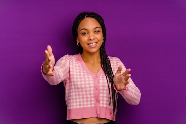 Jovem afro-americana isolada em uma parede amarela se sente confiante dando um abraço na frente